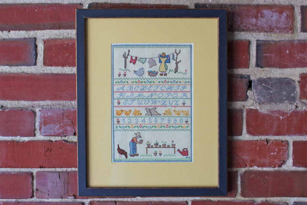 Framed Cross-Stitch Alphabet Sampler with Farm Chore Scenes