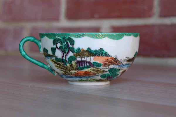 Delicate Japanese Porcelain Teacup Decorated with an Ornate Water and Landscape Scene