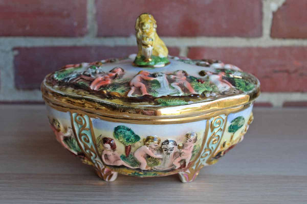 Italian Capodimonte Covered Dish with Raised Cherubs. Dogs, and Lion Finial