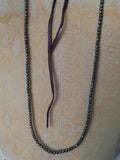 Alicia Van Fleteren necklace has dark pyrite attached to brown leather ties.