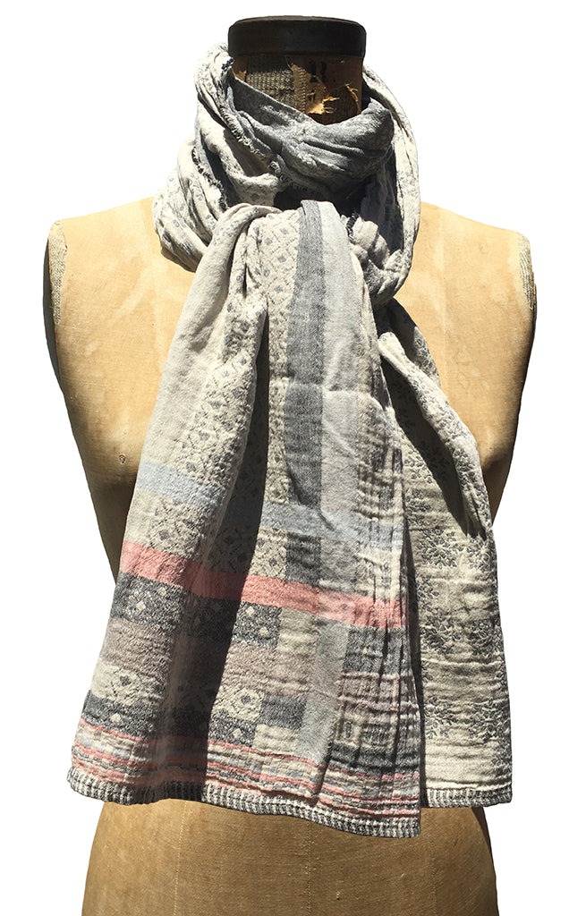 The Letol Daphne scarf has soft geometric and snowflake motifs in warm grey, greys with soft coral.