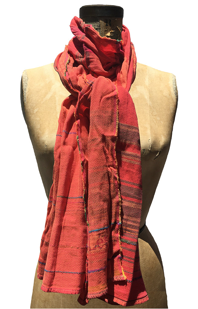 The Letol Desiree scarf has an intricate weave in warm oranges and reds with hints of blue and green.