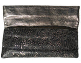 Flap up on Lousie Farnay black laser cut leather clutch, bronze backing