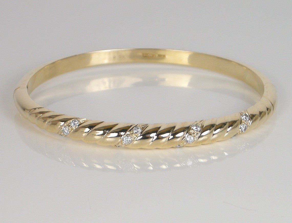 Gold and diamond bangle with a twist