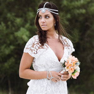 Bride is holding wedding flowers and wearing a silver head chain