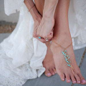 Bride putting on barefoot sandals for ceremony