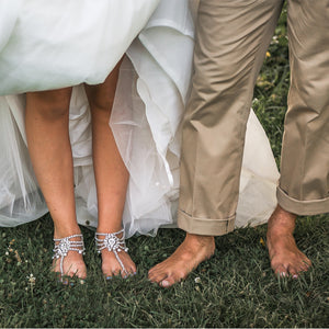 Bride is showing off her bare feet wearing bottomless sandals