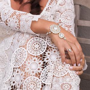 A bride is wearing custom made hand jewelry
