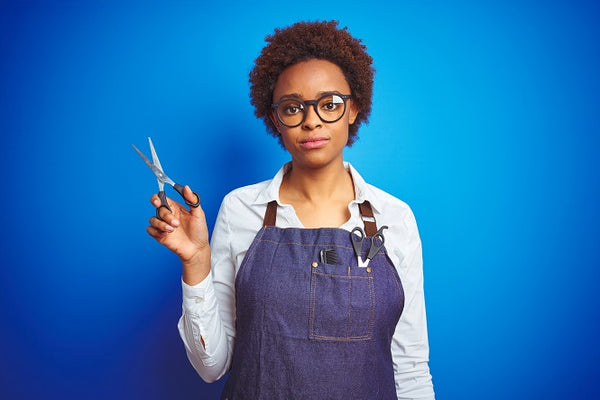 black woman with naturally curly hair against a blue backdrop wearing overalls and holding scissors