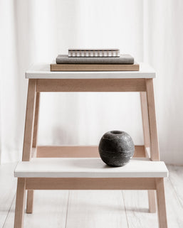 Different sized books stacked on a wooden stool