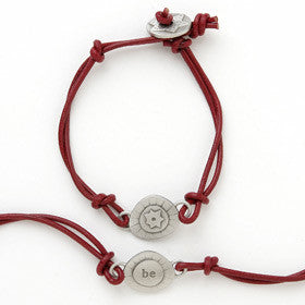 This bracelet has a pewter charm on colored leather with the word