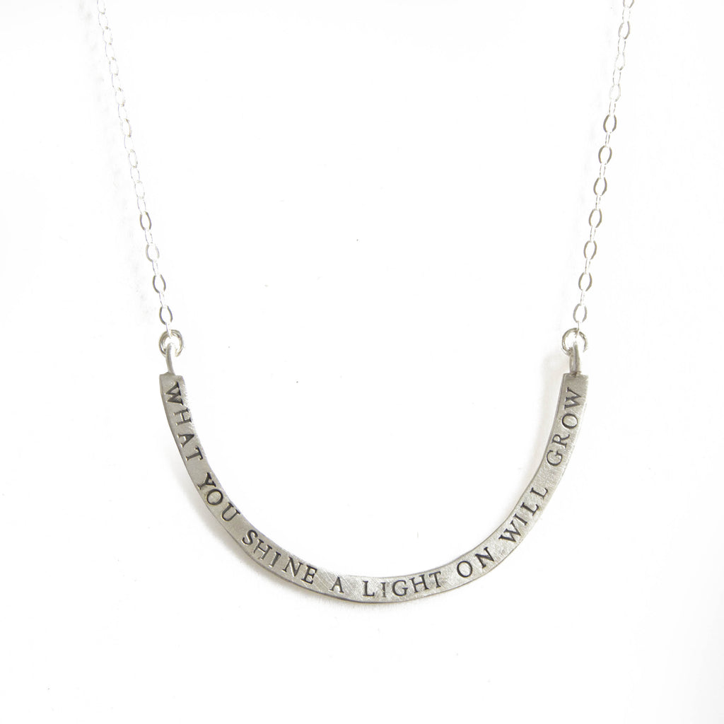 what you shine a light on cup half full necklace