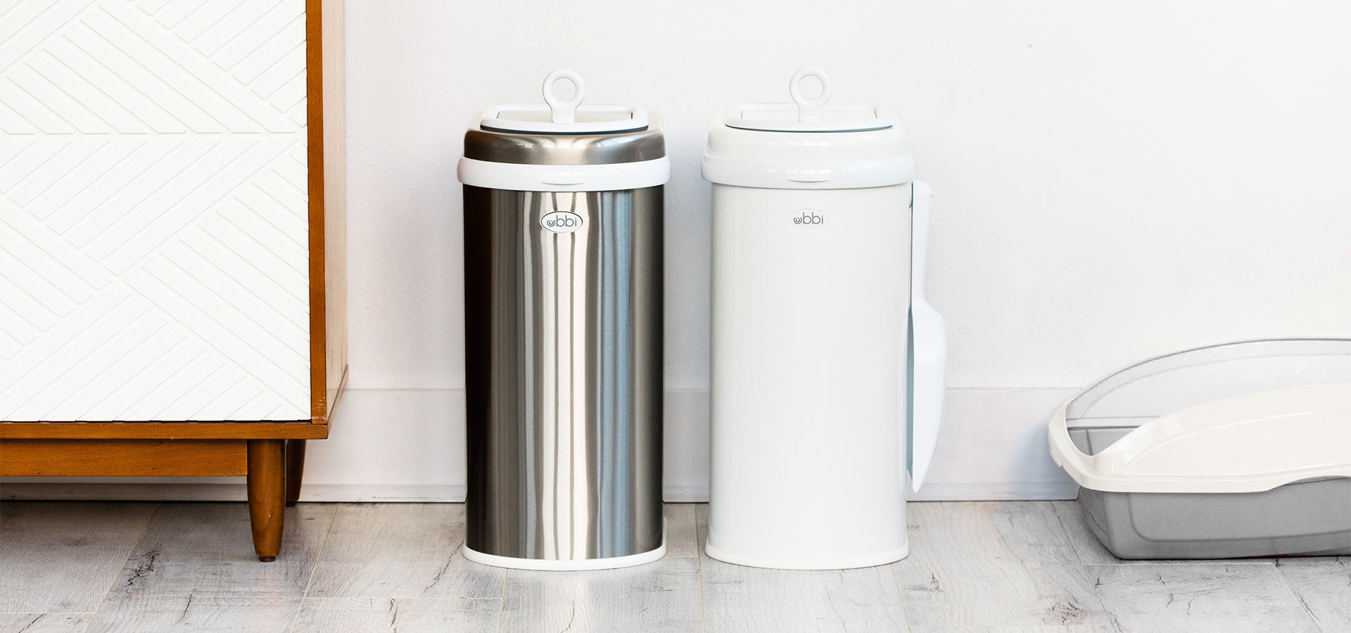 The chrome and white Ubbi pet waste pail side-by-side with a gray litterbox to the right