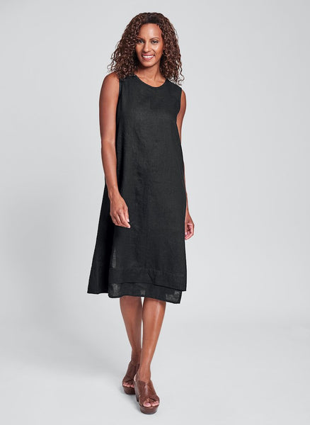 Vancouver Dress (shown in solid Eclipse), 100% Linen, round neckline, A-line shape, sleeveless, mid-length, asymmetric hem with pintuck detail, and asymmentric slit detail in back. FLAX Bold 2020.