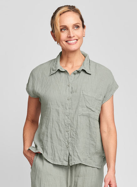 "Bijou Shirt (shown in Sage)- a collared linen blouse, woven in 100% Handkerchief-weight Linen (body), steam crunched to give it Urban's signature ""crinkled"" look, featuring drop shoulders that gently slip over the arm to form cap sleeves, with a chest pocket on the left, corozo buttons down the front, finished with side slits for added movement.  FLAX Urban II 2021"