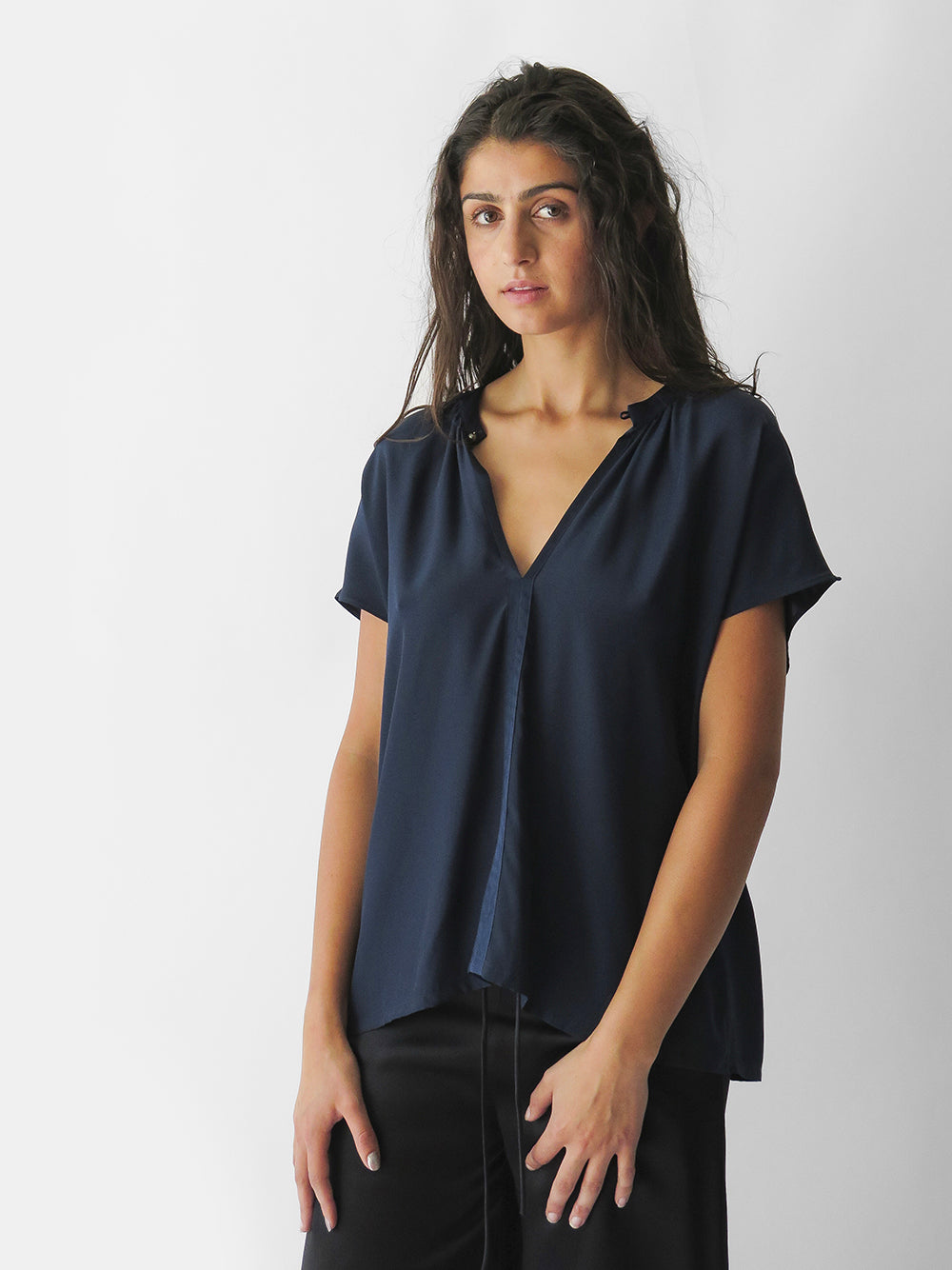 our timeless & essential cap sleeve blouse of matte faced silk charmeuse. v-neck with gathers at neckline & button loop closure. trimmed with satin detail. transitions between seasons & day to evening. made in usa. available online, berkeley 4th street, marin country mart, & row dtla.
