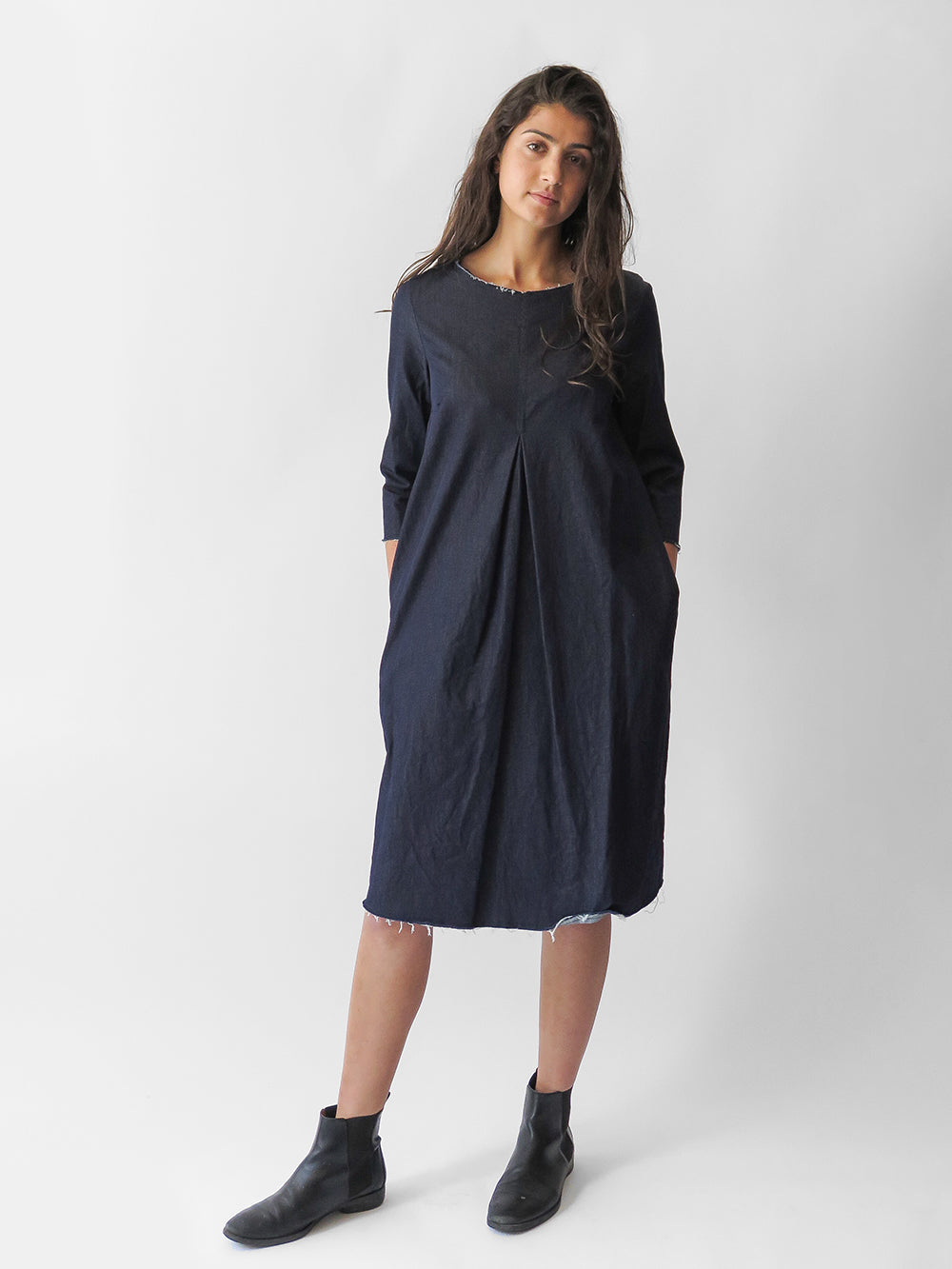 signature a-line dress in stretch dark denim with side pockets & 3/4 length sleeves. features pleated front & modern raw edges. our essential & timeless piece is ideal for seasonal & day-to-evening transition. shown with a casual ankle boot, can work with a wingtip or strappy heel. made in usa.