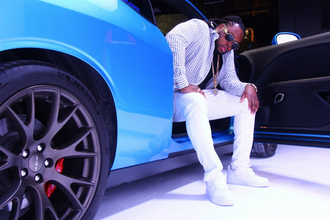 Young cake sitting in a blue car wearing all white