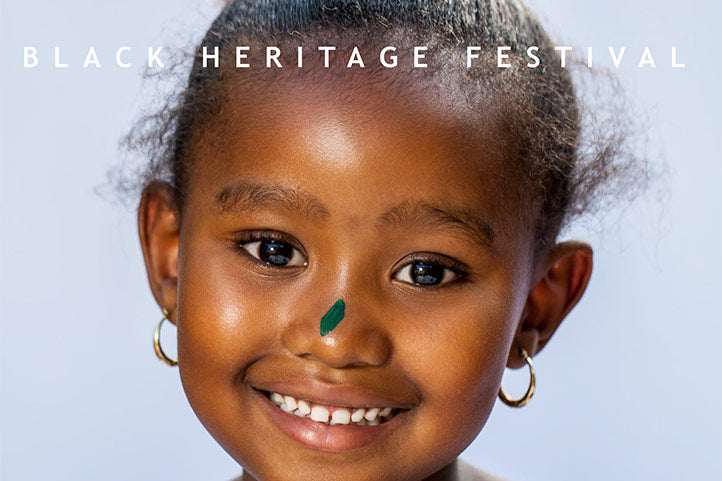Cheerful African-American Girl with a green painted hand.