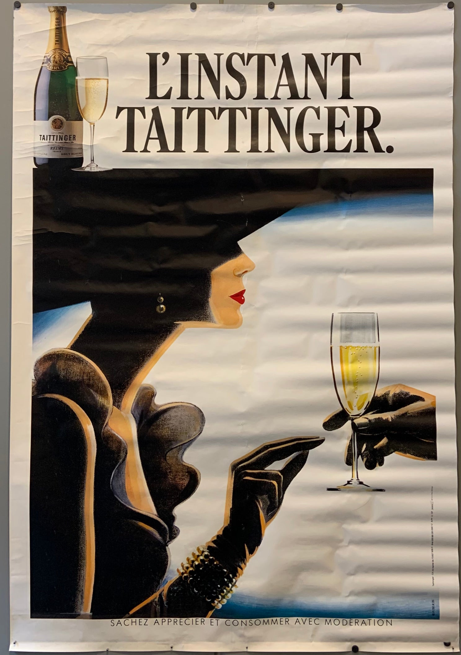 A poised model, her face in profile and her identity hidden by the shadow from her wide-brimmed hat, accepts a glass of champagne.