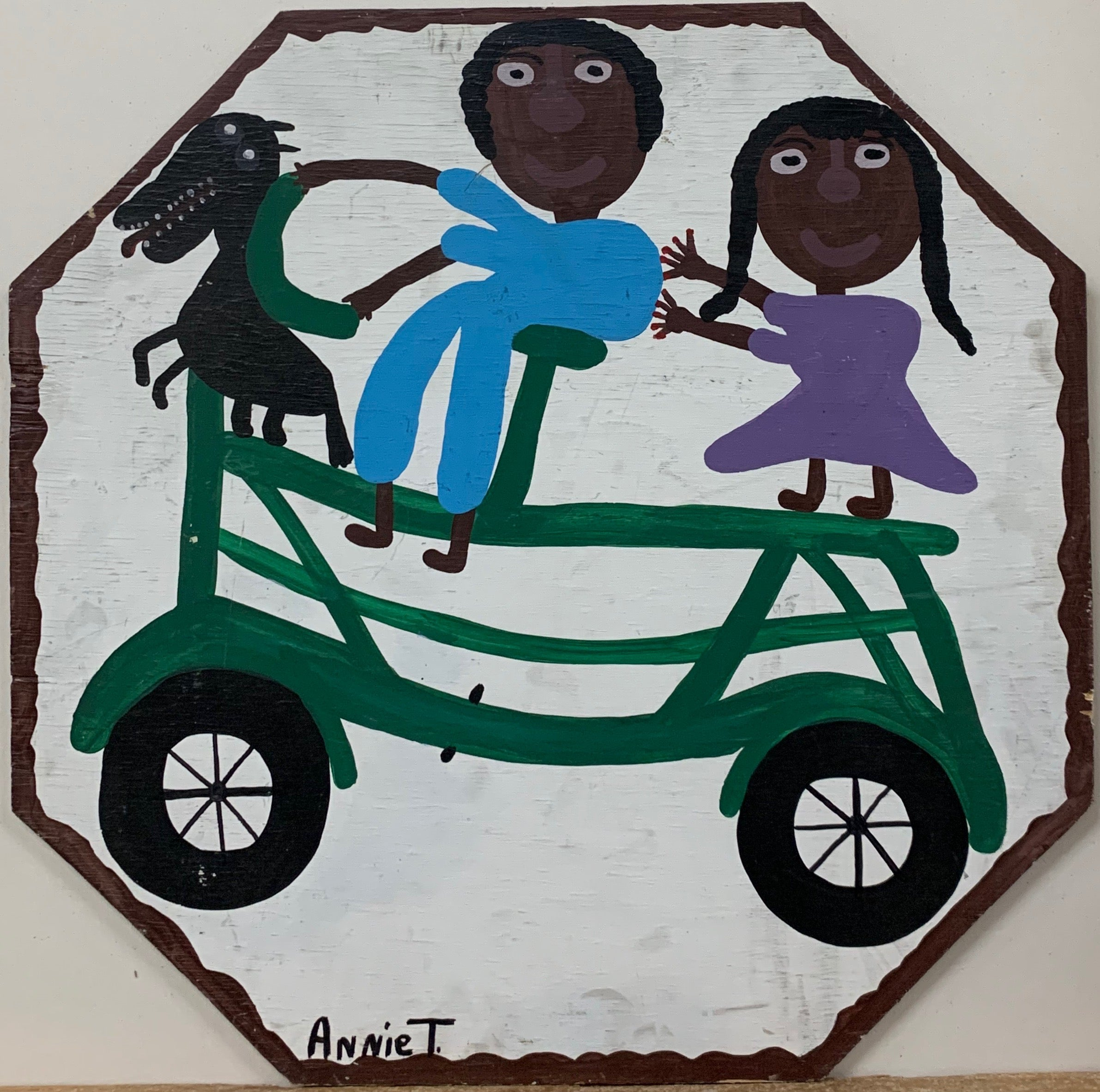 An Annie Tolliver painting of a man and a woman riding a green bicycle with their black dog  up front.