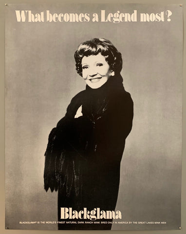 A smiling woman with short curly hair wraps herself in a fur coat. The text is on the top and the bottom in black.