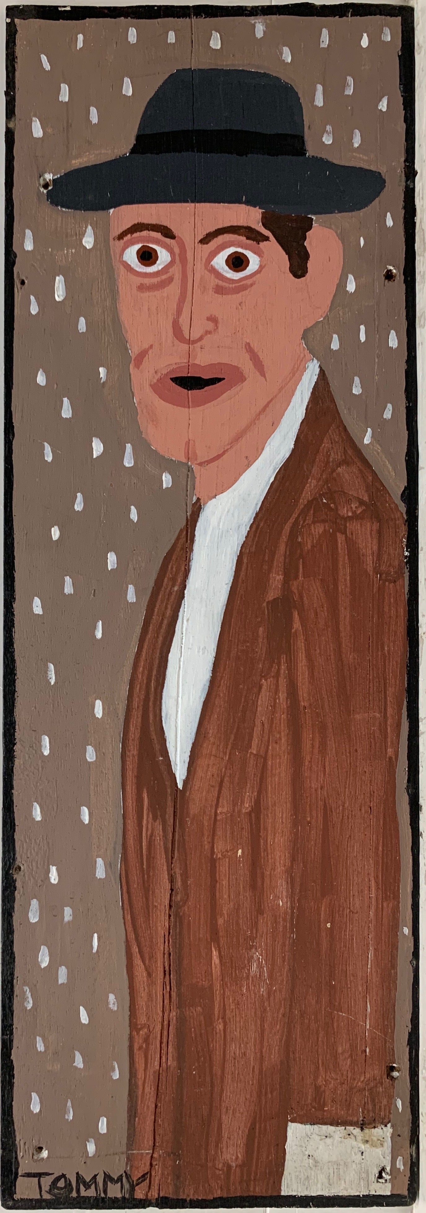 A Tommy Cheng portrait of Willem Dafoe in a black hat and a brown coat.
