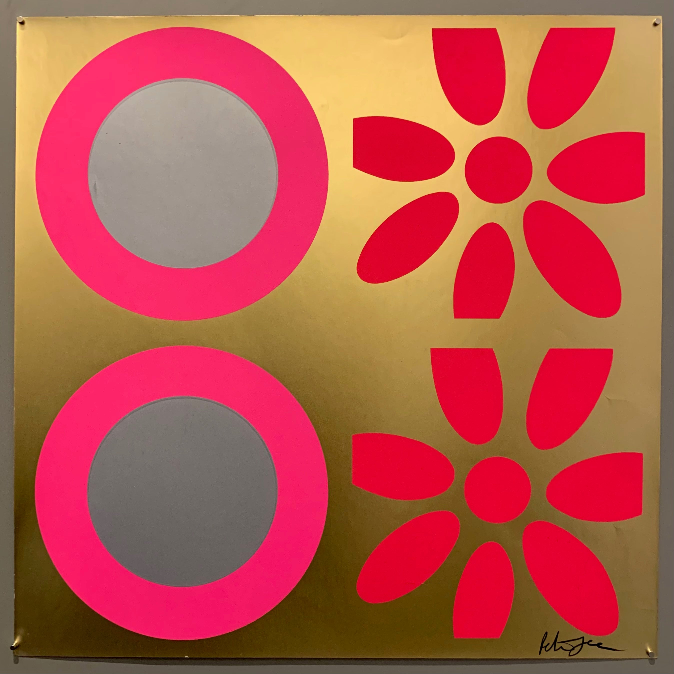 A square of four large motifs on paper. The colors are gold with hot pink and silver targets, the other is gold with bright pink targets.
