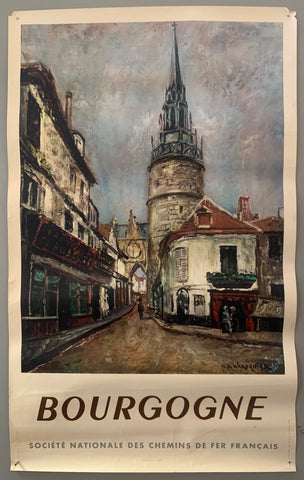 A image in the style of oil painting shows a street leading to a quaint row of shops and a church steeple. The poster has a white border with bold, all-caps, brown and grey writing.
