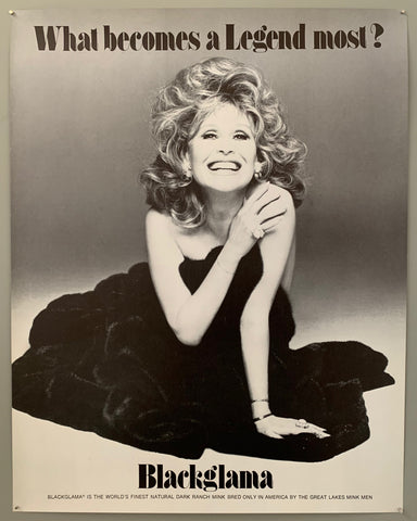 A blonde Suzy Knickerbocker sits on the floor covered in a mink coat. She smiles widely. The text is on the top and the bottom in black.