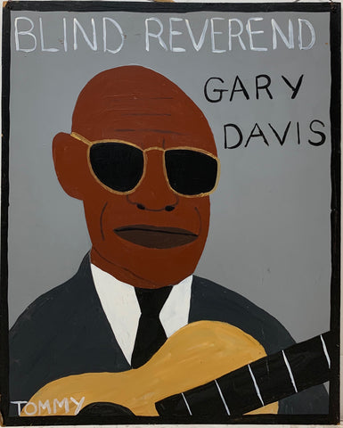 A Tommy Cheng portrait of Blind Reverend Gary Davis wearing a black tux, gold-rimmed sunglasses, and holding his brown wooden guitar.