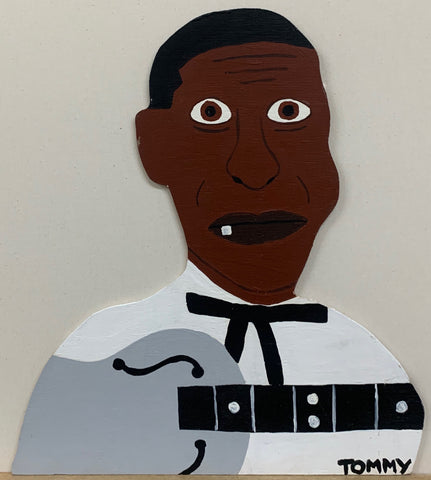 "Portrait of Eddie James ""Son"" House Jr. with one tooth sticking out of his mouth and a silver guitar in front of him."