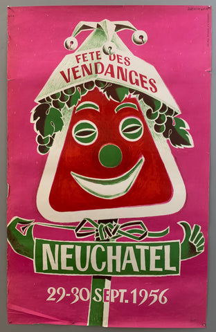 "A red sign with the name of the town on it has a face and hair made of grapes, as well as a jester hat with bells, The ""man"" is red and green and the background is pink. The writing is in white."