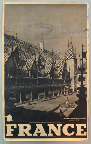 This poster is sepia toned with bold black-and-white writing at the bottom, as well as a tiny map of France. The photograph takes up the majority of the page.The photograph contains a view of a intricately designed hotel with a town square in the middle. The shadows are quite intense and this looks like a quaint countryside village.