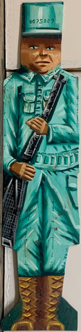 A Steve Keene double-sided painting of a soldier in a teal uniform and brown boots carrying a black rifle.