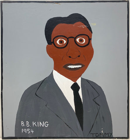 A Tommy Cheng portrait of B.B. King in a gray suit, black tie, and black glasses.