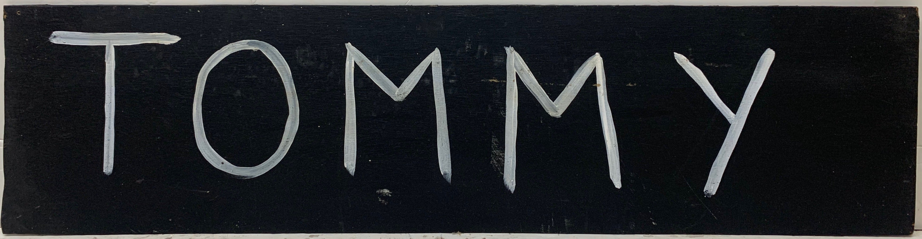 A Tommy Cheng painting of his signature, Tommy, painted in white against a black background.