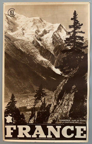 This poster is sepia toned with bold black-and-white writing at the bottom, as well as a tiny map of France. The photograph takes up the majority of the page.The photograph contains a wide view of snow-capped mountains and a far-away view of the town in the valley below. This is from a parallel mountain, and the view is slightly blocked by pine trees.