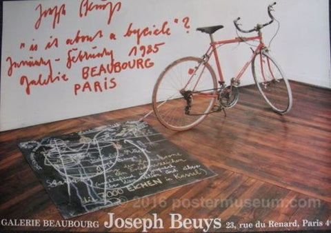 "Photograph of a red bicycle attached to a chalkboard lying on the ground with words and abstract lines drawn on it in white chalk. The bicycle and chalkboard are in a white room with a wooden floor. In the top left-hand corner of the photograph are the words ""Joseph Beuys ""is it about a bycicle"" ? January-February 1985 galerie Beaubourg Paris"" written in a messy red handwriting. Across the bottom of the poster in a white typeset are the words ""Galerie Beaubourg Joseph Beuys 23, rue du Renard, Paris 4eme."