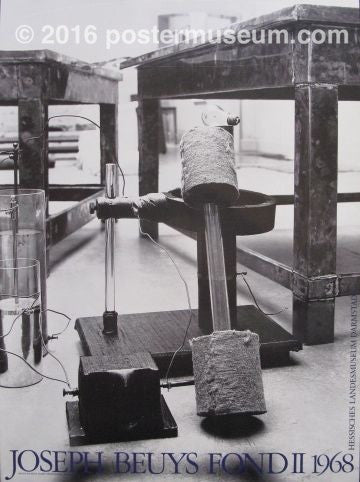 "Black and white photograph of a copper plate connected to a battery, surrounded by various chemical apparatuses. On the bottom of the poster written in blue typeset is ""Joseph Beuys Fond II 1968."""