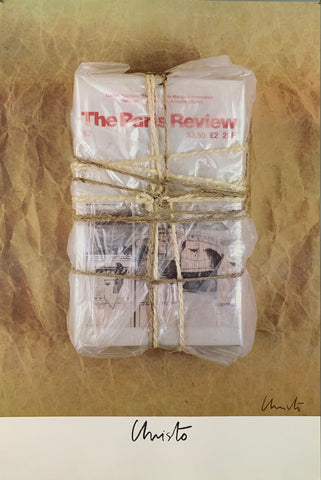 A photograph of a plastic wrapped stack of The Paris Review wrapped in twine on a tan background.