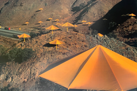 A vibrant colored photograph of a smatter of yellow umbrellas against brown hills.