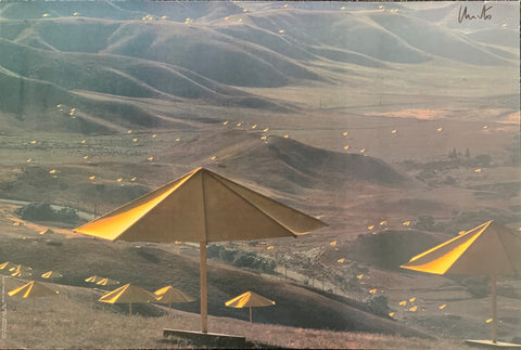 A colored photograph of yellow umbrellas dotting a hill.