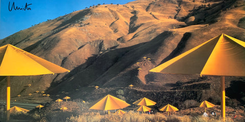 A landscape photograph showing a smattering of yellow umbrellas against the brown countryside.