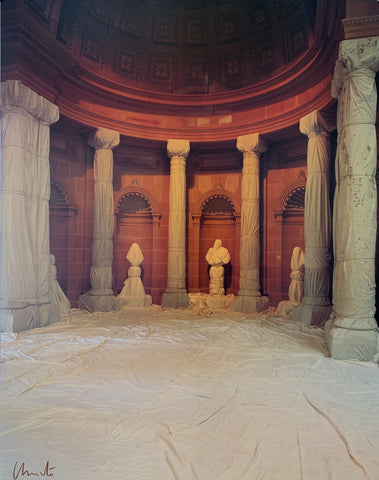 A colored photograph of wrapped columns in a domed red room.