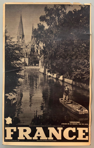 This poster is sepia toned with bold black-and-white writing at the bottom, as well as a tiny map of France. The photograph takes up the majority of the page.The photograph contains a view of a serene canal with a man boating down it. The river is framed by trees and in the background a gothic church is shown.