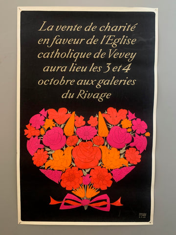 Black background with tan colored writing in italics. Bouquet of red, pink, and orange flowers in the shape of a heart is under the writing.