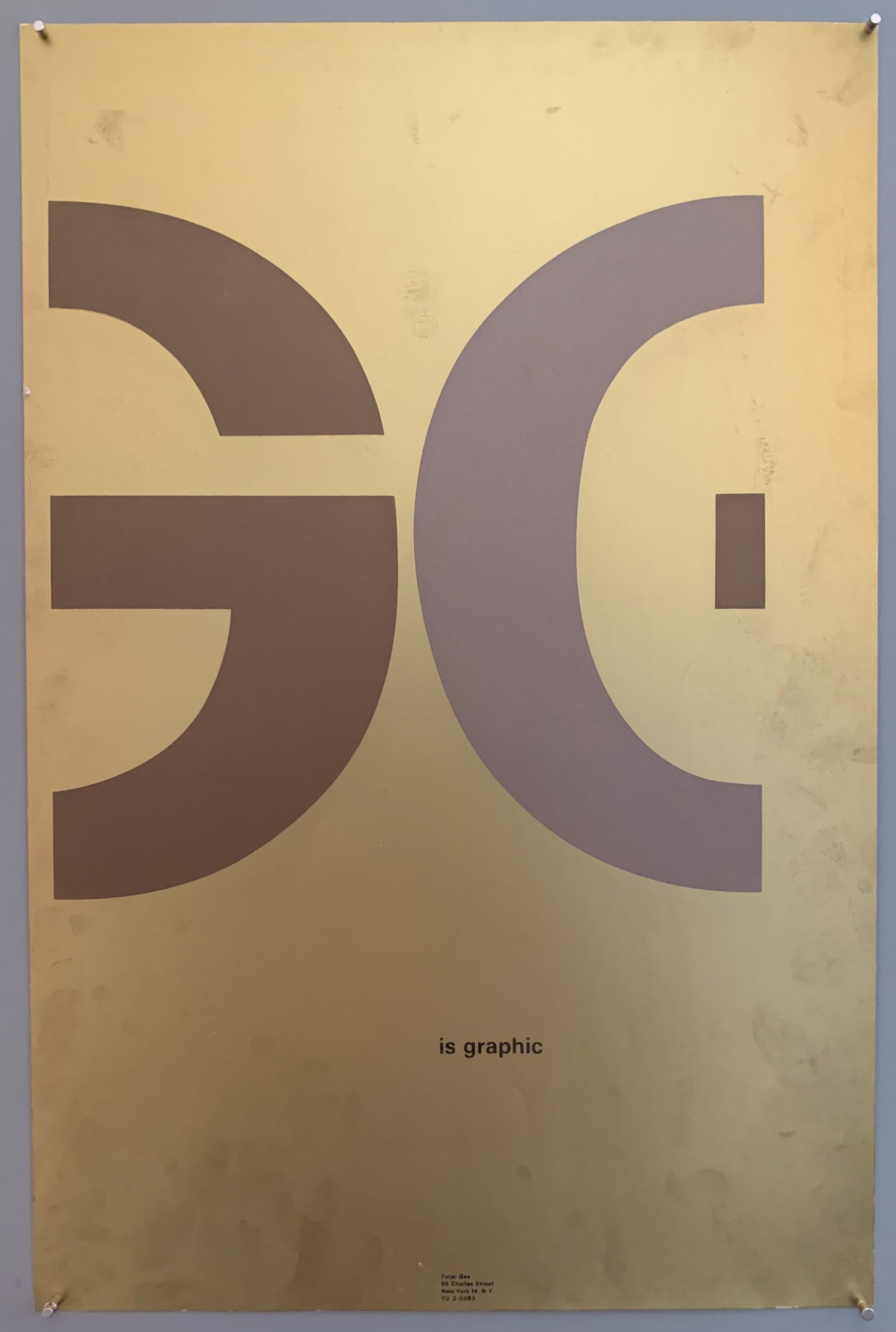 "A mostly plain paper has G and part of an E written across the middle in huge font. ""is graphic"" is written below in smaller font, and the studio address is written much smaller towards the bottom. The colors used in this are brown, grey, and a metallic gold paper."