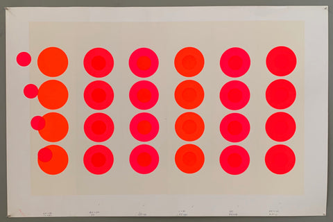 "These neon targets, in blinding shades of orange, pink, and red. The ""bullseyes"" are spilling off the print on the left side, causing an illusion of movement. The panels are all light cream colors, making the neon really stand out. The border of the poster is white."