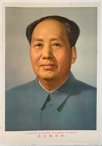 A color photograph of Mao Zedong in a blue shirt with red chinese characters underneath.